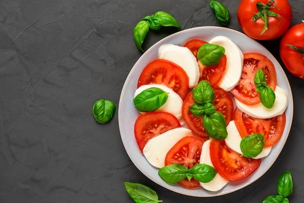 Caprese salad with ripe tomatoes and mozzarella cheese, fresh basil leaves. italian food