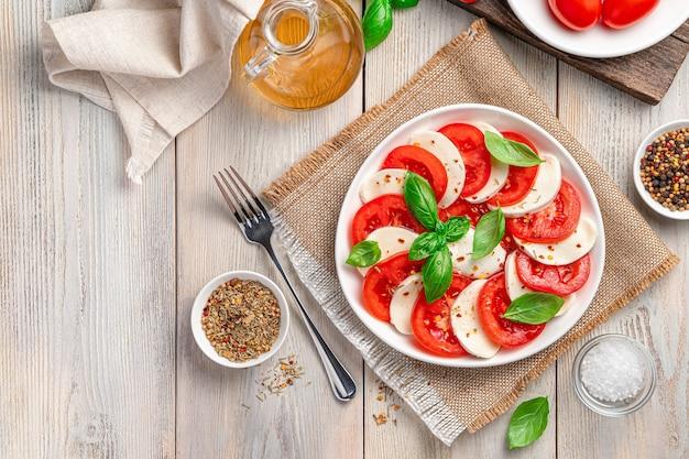 Салат капрезе с нарезанными помидорами сыр моцарелла, оливковое масло и базилик