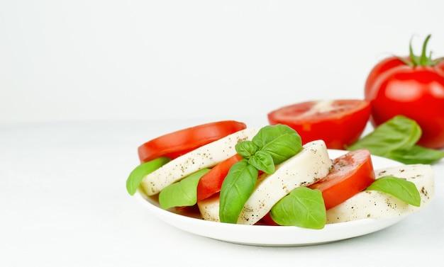 회색 콘크리트 배경에 토마토 바질과 모짜렐라를 곁들인 카프레제 샐러드