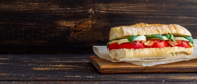 Сэндвич капрезе с помидорами, моцареллой, базиликом и беконом. здоровое питание. итальянская кухня.
