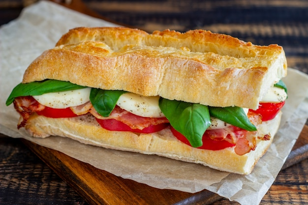 トマト、モッツァレラチーズ、バジル、ベーコンのカプレーゼサンドイッチ。健康的な食事。イタリア料理。