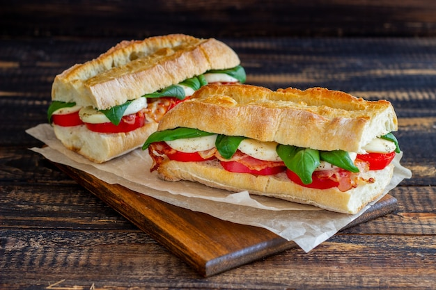 Caprese sandwich with tomatoes, mozzarella, basil and bacon. healthy eating. italian cuisine.