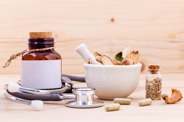 Capsule of herbal medicine with stethoscope wooden background.