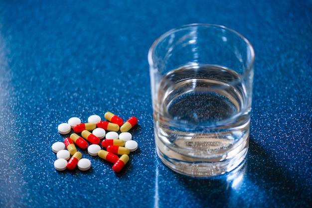 Капсулы и таблетки на стакан воды на столе