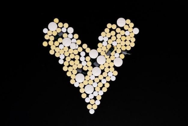 白と黄色のカプセルと錠剤。ハートの形。黒の背景