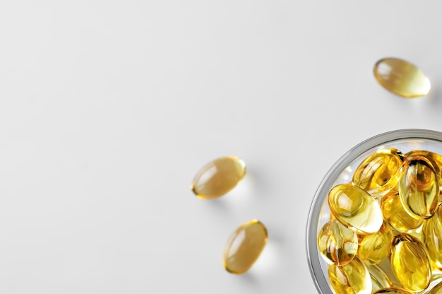 Capsules of fish oil in a glass bowl