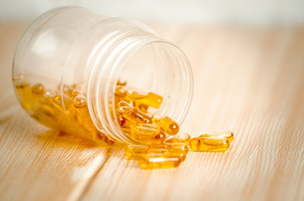 Capsules of fish oil spilled out open container.