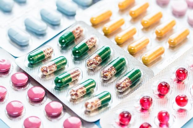 ブリスターパックのカプセルホイルブリスターパックのさまざまな錠剤青い表面に薬薬