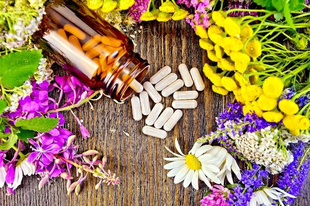 Капсулы в открытой коричневой банке и на столе, свежие цветы кипрей, пижма, ромашка, клевер, тысячелистник, таволга, листья мяты на фоне деревянных досок сверху