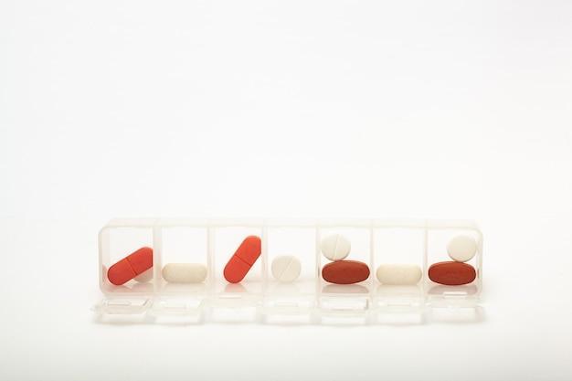 カプセルは、白い背景の上のピルボックスにあります。錠剤を1週間梱包するための箱。すべてのタブレットの家