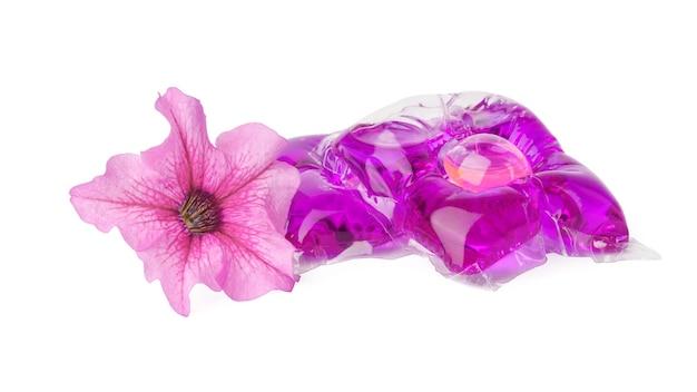 Капсулы моющего порошка и цветок петунии, изолированные на белом фоне. л