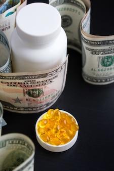 魚の油と黒の背景にドルのカプセル。高価な薬。医薬品の不足。コロナウイルス
