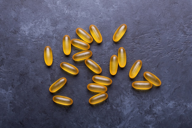 Capsules omega 3 on dark stone background close up health care concept