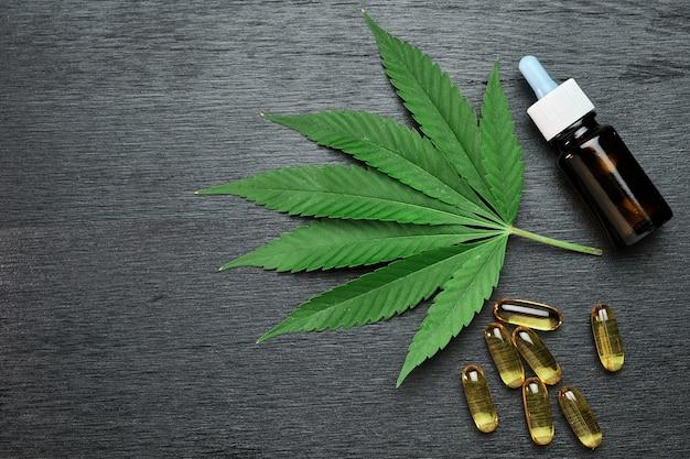 Капсулы или таблетки и бутылка с каннабисом cbd или конопляным маслом на листе марихуаны на черном