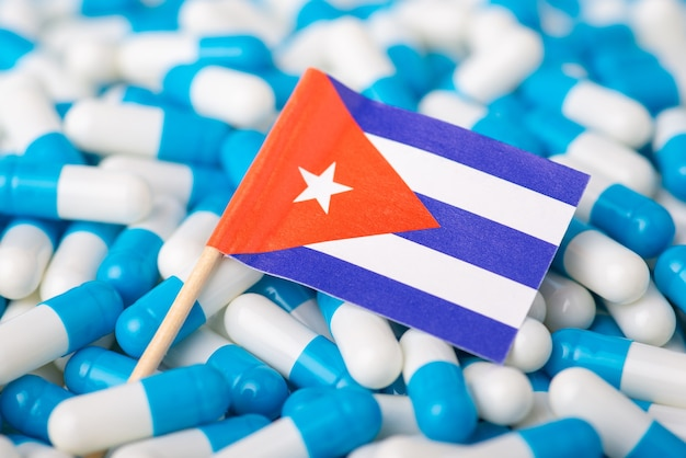 Capsules and pills laying on flag of cuba