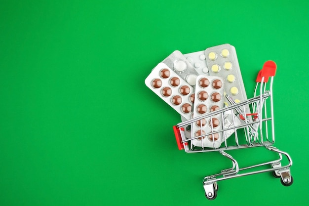 Capsules,pills,medicines in blisters on green background in shopping cart.