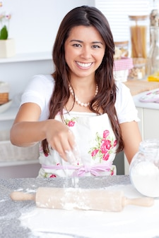 Captivating asian woman baking in her kitchen