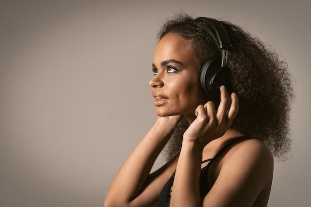 音楽で離れてキャプチャ音楽を聞いて横向きに見上げるアフリカ系アメリカ人の少女