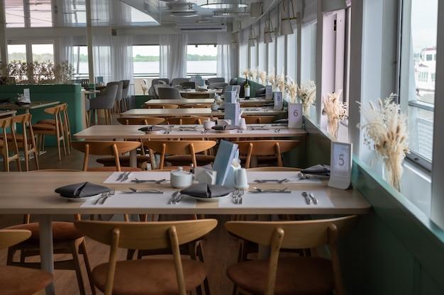 유람선에서 레스토랑의 내부 모습을 포착하십시오. 작은 유람선 레스토랑에서 테이블의 행입니다. 파노라마 창