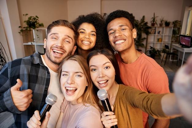 スマートフォンを使用して自分撮りをしている陽気な若い多文化の友人の瞬間をキャプチャします
