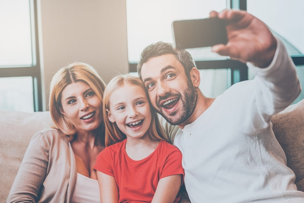 Capturing a bright moment together. happy family of three bonding to each other and smiling while father photographing them with smart phone