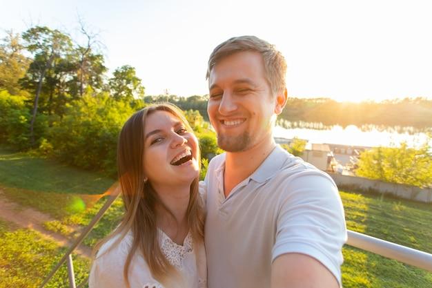 밝은 순간을 포착합니다. 야외에 서 있는 동안 카메라에 셀카를 만드는 즐거운 젊은 재미있는 사랑하는 부부