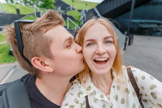 明るい瞬間を捉えます。自撮りをするうれしそうな若い愛情のあるカップル。かなりの観光客が旅行ブログのために面白い写真を作ります