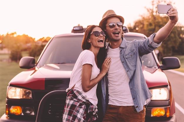 Снимать удовольствие. красивая молодая пара приклеивается друг к другу и опирается на свой пикап, делая селфи