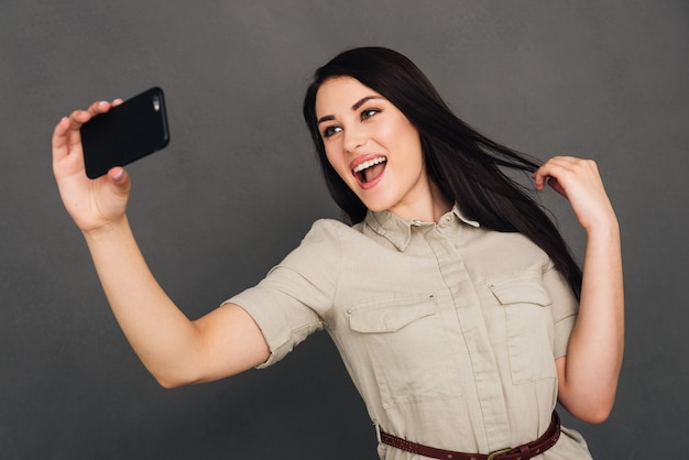 Capturing fun. beautiful young woman making selfie by smart phone and smiling while standing