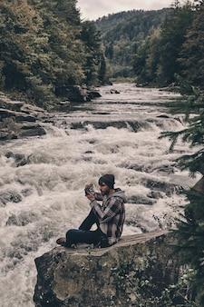 Сохранение воспоминаний. красивый молодой современный человек фотографирует сидя на скале у реки