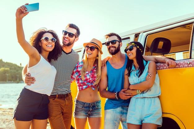 Запечатлеть летнее веселье. группа счастливых молодых людей, связанных друг с другом и делающих селфи, стоя возле своего ретро-минивэна