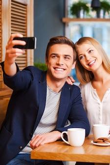 빛나는 순간을 포착합니다. 스마트 폰으로 셀카를 만드는 동안 카페에서 서로 결합하는 아름다운 젊은 사랑의 커플