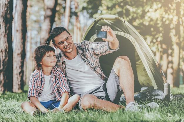 Запечатлеть яркие моменты. веселый отец и сын сидят возле палатки во время кемпинга в лесу