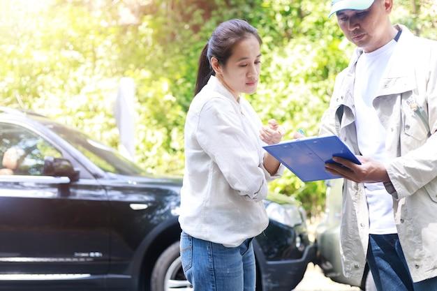 자동차 사고 자동차 충돌 사고에 대해 보험 에이전트에 얘기하는 여자. 보험 대리인
