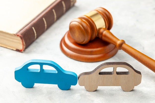 Car accident. judge gavel and two cars collided. car insurance solution.