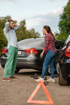 Дтп на дороге, мужчина и женщина разбираются. автомобильная авария, знак аварийной остановки. разбитый автомобиль или поврежденный автомобиль, автокатастрофа на шоссе