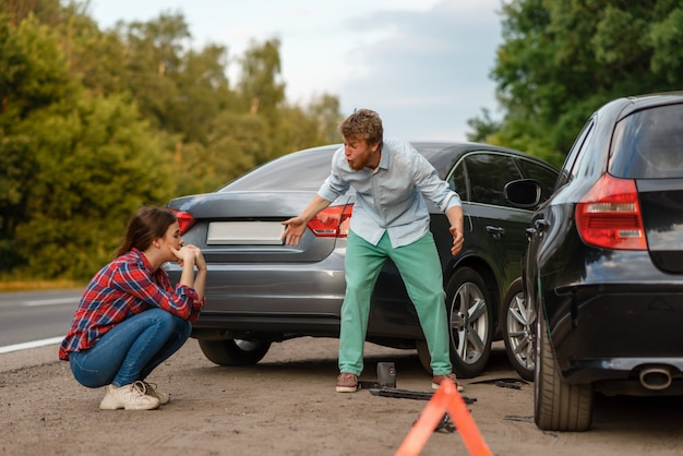 Car accident on road, male and female drivers are sorted out. automobile crash, emergency stop sign. broken automobile or damaged vehicle, auto collision on highway