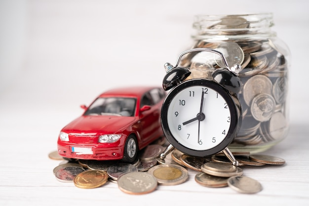 Car and alarm clock on coins.