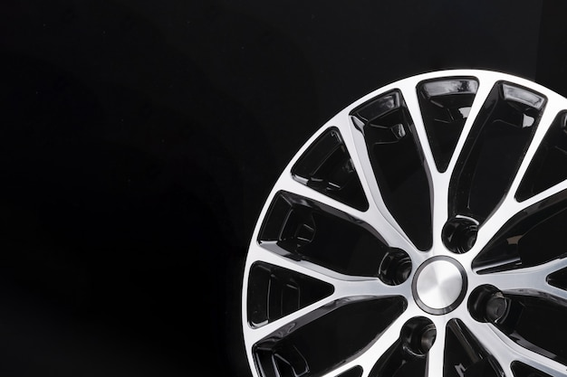 Car alloy wheel black and white beautiful modern design, on a black background, close-up element, thin spokes