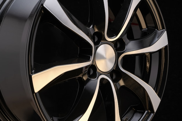 Car alloy wheel close-up of the disc element, curves smooth lines of the wheel spokes, polished front surface.