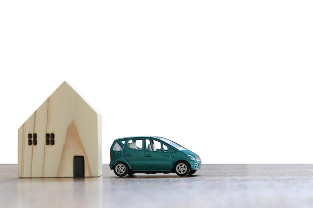 車と白で隔離され、木の床におもちゃの家とクリッピングパスがあります。