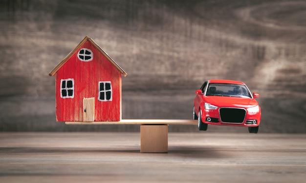 균형에서 나무 저울에 자동차와 집.