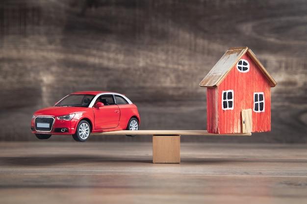 木の天秤に乗った車と家のバランス。