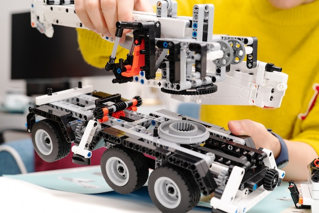 Car assembly kit, woman assemble a very complicated and common car truck toy.