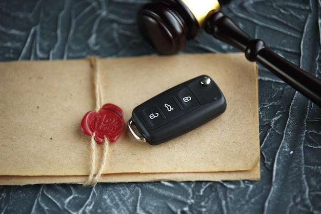 カーオークションのコンセプト-木製の机の上のガベルと車の鍵