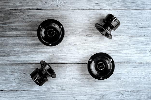 Автомобильные аудиосистемы черные автомобильные динамики лежат на белом деревянном фоне