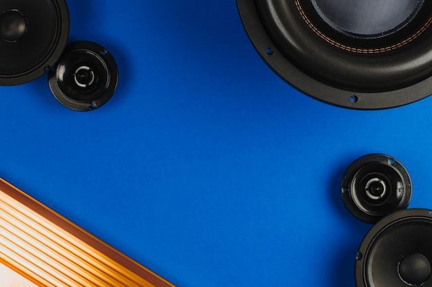 Автозвук автомобильные динамики черный сабвуфер и усилитель звука на синем фоне копией пространства