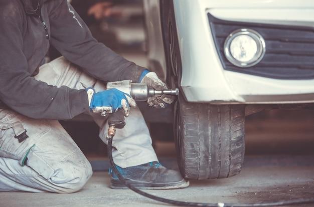Автомобиль, автомеханик с заменой шин, колес на авто гайковертом, сервисный центр