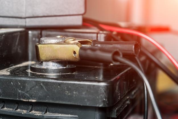 Зарядка автомобильного аккумулятора, клеммы и провода для зарядки аккумулятора