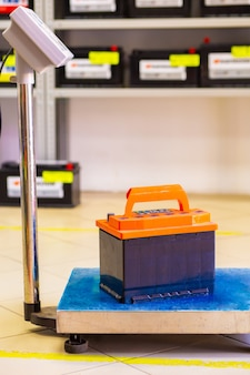 Car battery stands on floor scales against the background of a blurred rack